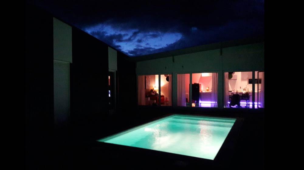 Vue de la maison avec piscine de nuit